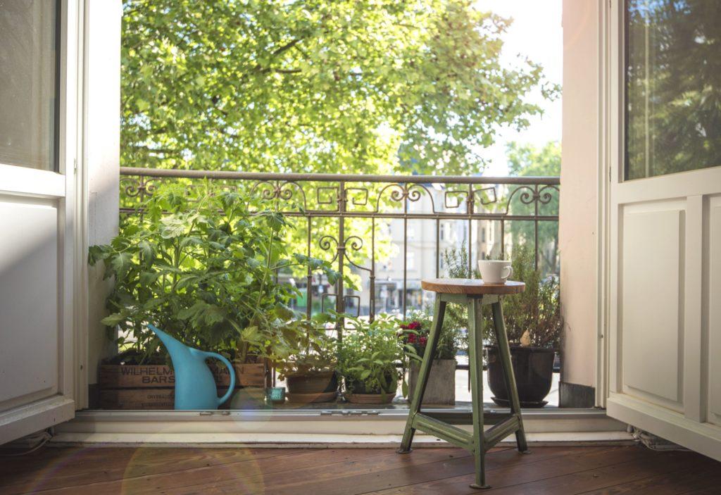 Balkon mit verschiedenen Kräutern, die Türen zum Balkon sind weit geöffnet