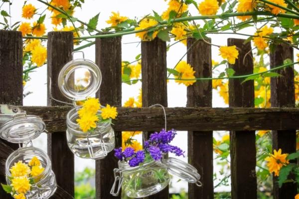 Man erkennt eine Blumendekoration am Gartenzaun