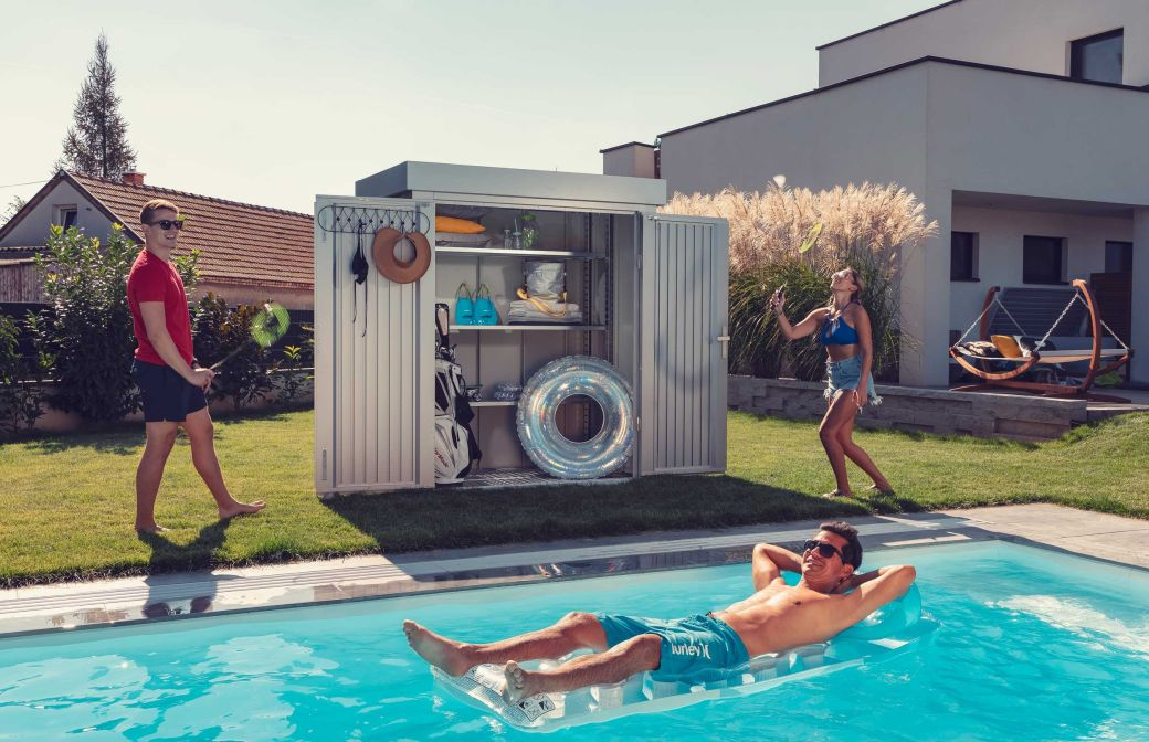 Im Bild ist eine GUARDI Gartenhütte zu sehen. Im Vordergrund spielen Menschen im Garten