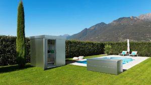 Gartenhaus und gartenbox stehen auf einer Wiese neben einem Pool, umringt von einem Sichtschutz aus Pflanzen