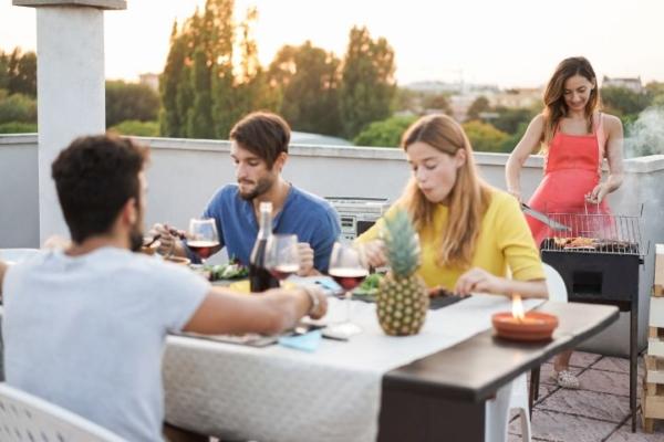 Freunde sitzen be´quem am Esstisch und im Hintergrund wird gegrillt.