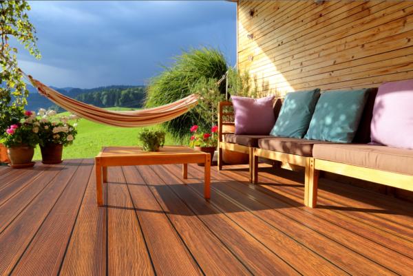 Terrassenprofil aus Aluminium in Holzoptik, dahinter hängt eine Hängematte