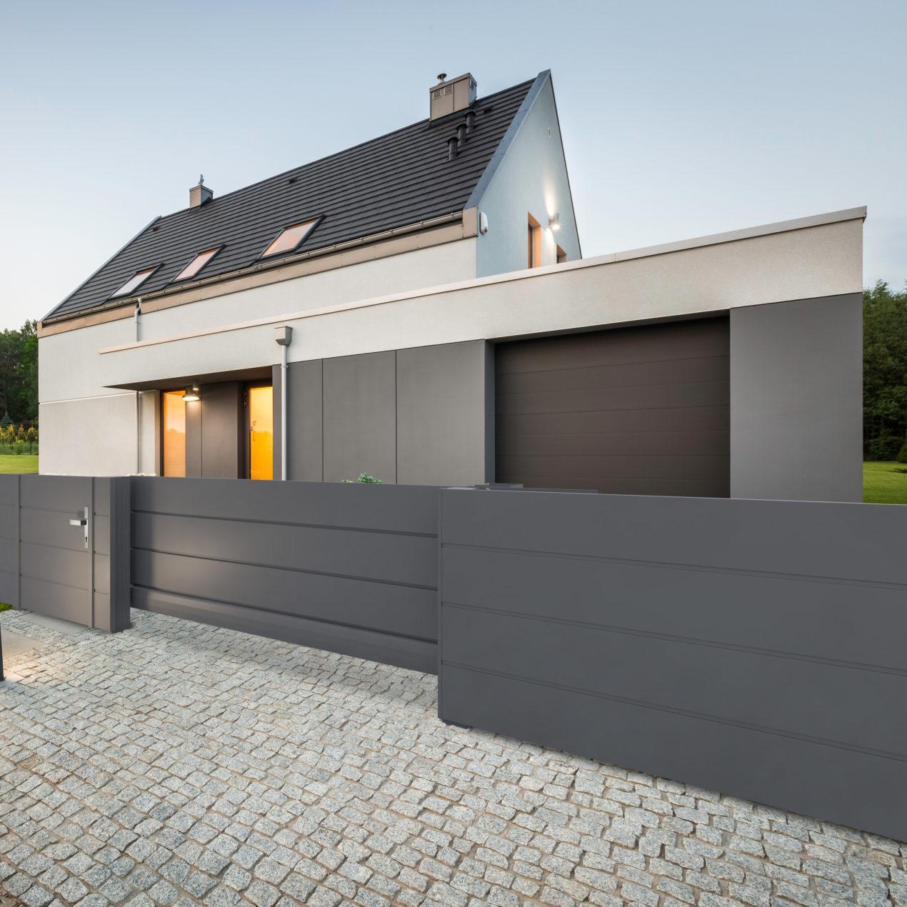 Sichtschutzzaun und Tor vom Modell Vista in anthrazit, im Hintergrund ein Haus in gleicher Farbe
