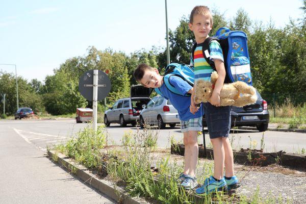 Man erkennt zwei Schulkinder beim überqueren der Straße