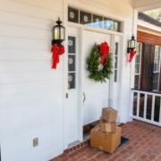 Drei Pakete liegen vor einer weißen Haustür