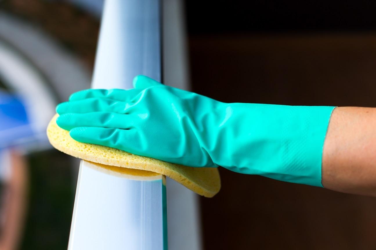 Eine Hand mit Gummihandschuh säubert einen Balkon