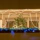 Balkon geschmückt mit verschiedensten Lichterketten, am Balkon steht ein Weihnachtsbaum