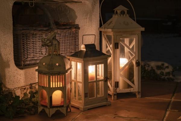 Drei Laternen aus Holz mit Kerzen darin stehen auf einer Steinplatte an der Hauswand