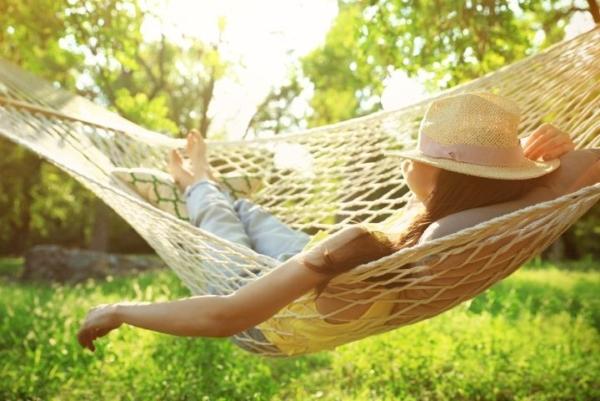 Eine Frau liegt in einer Hängematte und entspannt, ein Strohhut ist übers Gesicht gelegt