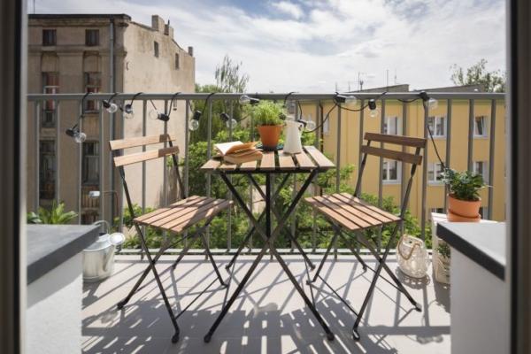 Man erkennt zwei hölzerne Stühle auf einem Balkon