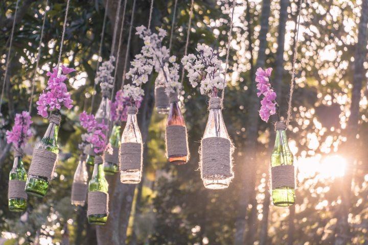 man erkennt aufgehangene Flaschen mit Blumen drinnen