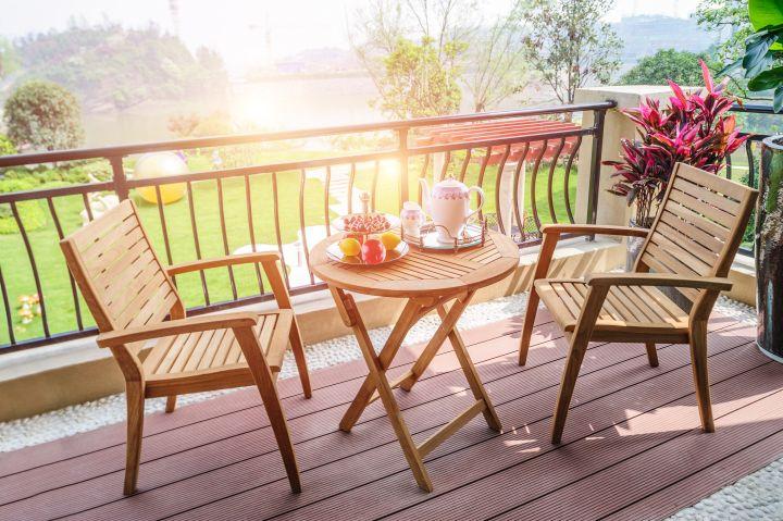 Man erkennt zwei Stühle aus Holz. Jene stehen auf einem Balkon. Im Hintergrund geht die Sonne unter