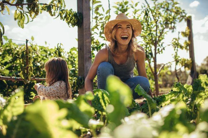 Man erkennt ein fröhliche Frau, die im Garten arbeitet