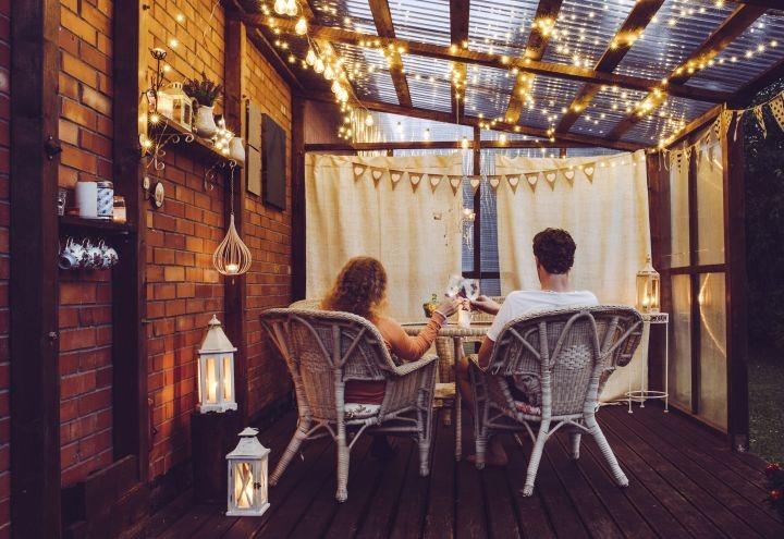 man erkennt zwei Menschen, welche unter einem Dach von Lichterketten sitzen