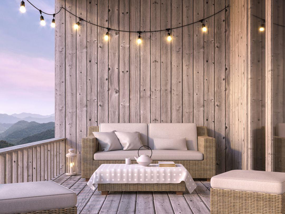 man erkennt eine gemütliche Sitzecke auf einem hölzernen Balkon