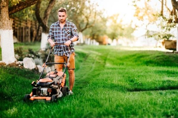 Man sieht einen jungen Mann, der mit seinem Rasenmäher über eine grüne Rasenfläche geht