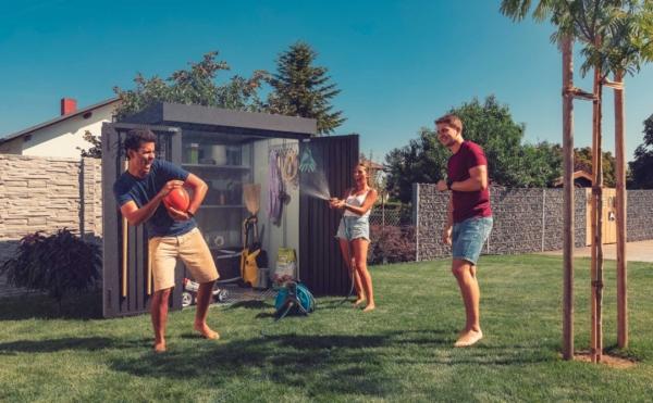 Eine Gruppe junger Menschen hat im Sommer Spaß im Garten, dahinter steht eine geöffnete Gartenhütte aus Stahl in anthrazit