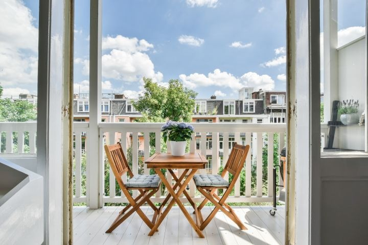 auf dem Bild sind 2 Holzsessel zu sehen. Jene sind auf einem weißen Balkon plaziert
