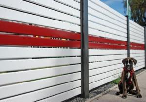 Sichtschutzzaun Modell Nouveau von GUARDI aus Aluminium in zweifärbiger Ausführung, davor sitzt ein Hund