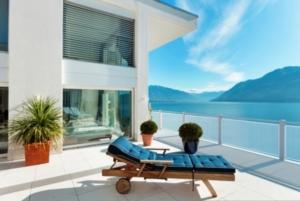 Balkongeländer in weiß mit Lochblech begrenzt eine Terrasse, auf der eine Liege steht mit Blick auf einen See