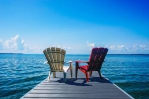 Blick von einem Steg mit zwei Stühlen und Terrassendielen aus Aluminium aufs Meer