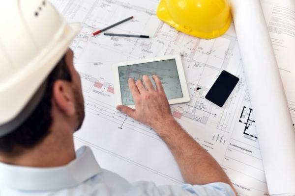 Man erkennt einen Bauarbeiter oder Architekten, der gerade einen Plan anfertigt