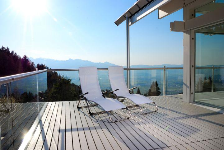 Man erkennt zwei Liegestühle auf einer Terrasse. Im Hintergrund sind Berge und Felder zu sehnen