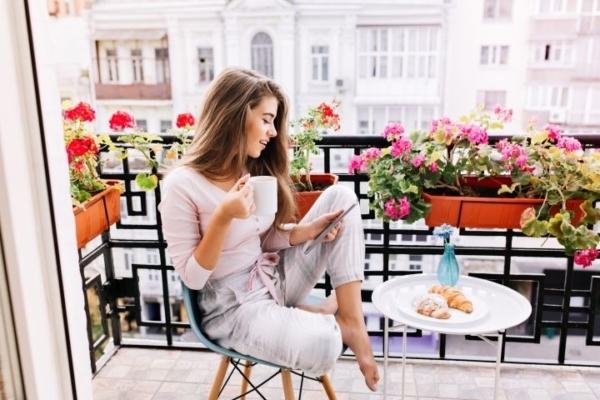Ein junges Mädchen sitzt auf dem Balkon, schaut in ein Tablet und am Balkongeländer sind einige Blumen zu sehen.
