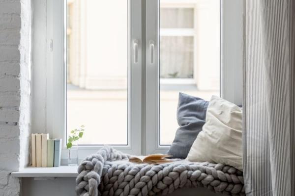Eine Fensterbank umfunktioniert zu einer Sitzbank mit einer Decke und Kissen
