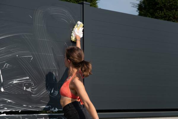 Mädchen wäscht im Bikini einen Sichtschutzzaun aus Aluminium in anthrazit