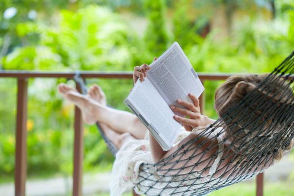 Frau liegt entpsannt in der Hängematte mit einem Buch