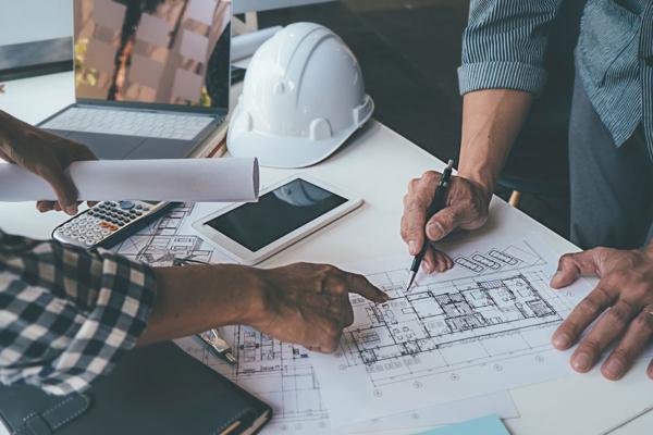 Man erkennt zwei Hände, die gerade auf einem Bauplan für ein Grundstück etwas einzeichnen. Daneben liegen Helm, Handy und sonstige Utensilien