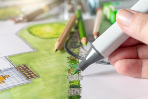 Großaufnahme eines Zeichenstifts, mit dem gerade eine Grünfläche und ein Gartenzaun gezeichnet wird