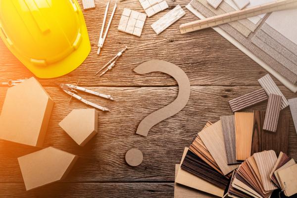 Auf einem Tisch liegen Muster verschiedener Materialien wie Holz, Metall oder Kunststoff, dazwischen liegt ein Fragezeichen