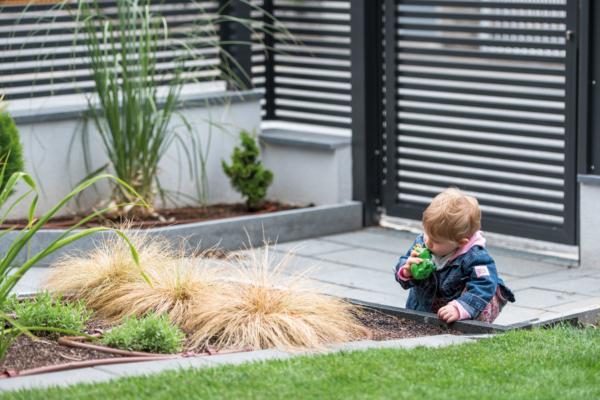 Kleines Kind spielt in einem Garten, der mit einem Gartenzaun aus Aluminium umzäunt ist