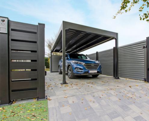 Ein Auto parkt in der Einfahrt unter einem Carport aus Aluminium, dazu passend in der gleichen Farbe ist ein Sichtschutzzaun aus Aluminium in anthrazit zu sehen