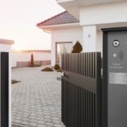 Geöffnetes Gartentor aus Aluminium und eine passende Briefkastensäule in anthrazit