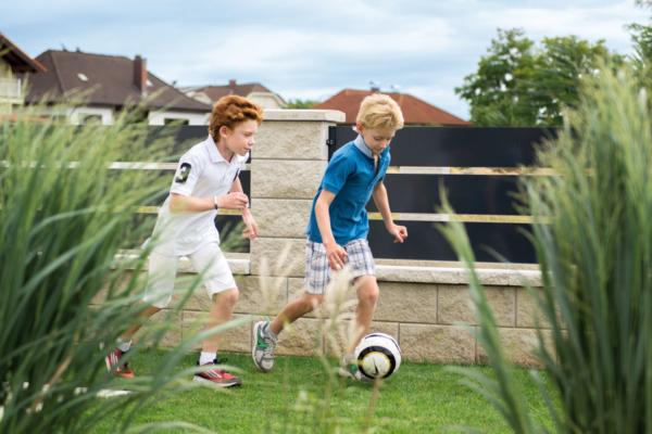 Zwei Jungs spielen Fußball im Garten, dahinter ein moderner Sichtschutzzaun aus Aluminium mit Querlatten