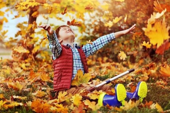 Ein Junge sitzt am Boden in einem Laubhaufen und spielt mit den Blättern