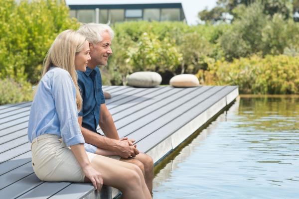 Ein mittelalterliches Ehepaar sitzt an einem Teich auf einem Steg mit Terrassendielen aus Aluminium in grau und lässt die Füße ins Wasser baumeln