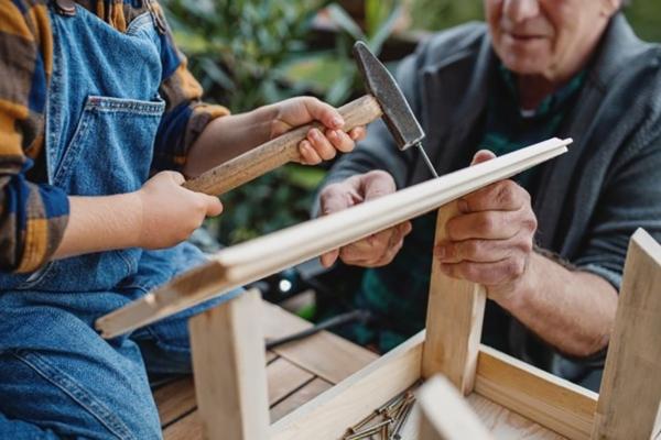 Ein kleiner Bub hält einen Hammer und schlägt damit einen Nagel in ein Holz, das von einem Mann gehalten wird