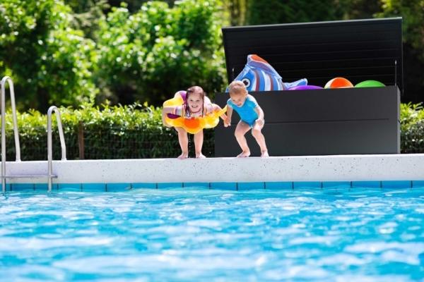 Zwei Kinder springen gerade in einen Pool, dahinter steht eine Gartenbox geöffnet und gefüllt mit Spielsachen für den Pool