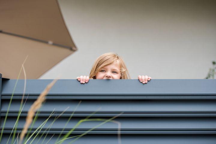 Man erkennt ein Kind, das über den Zaun schaut