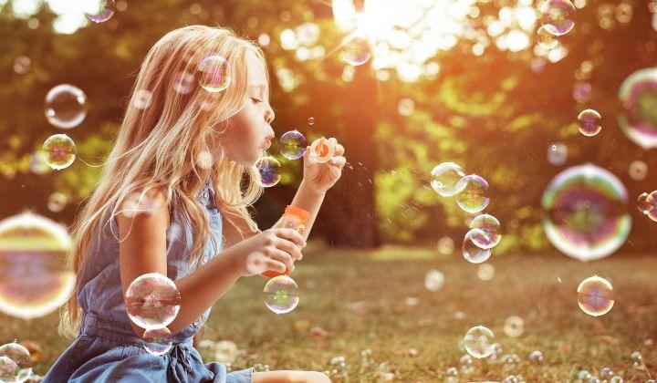Man sieht ein kleines Mädchen, dass mit Seifenblasen spielen
