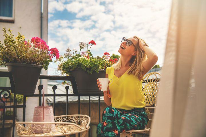 Man erkennt eine Frau auf einem Balkon. Sie lächelt und hält einen Kaffee in der Hand.