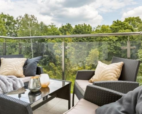 Man erkennt einen Balkon mit bequemen Balkonmöbeln