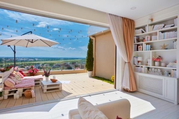 Man erkennt eine gemütlich eingerichtete Gartenlounge auf einer Terrasse