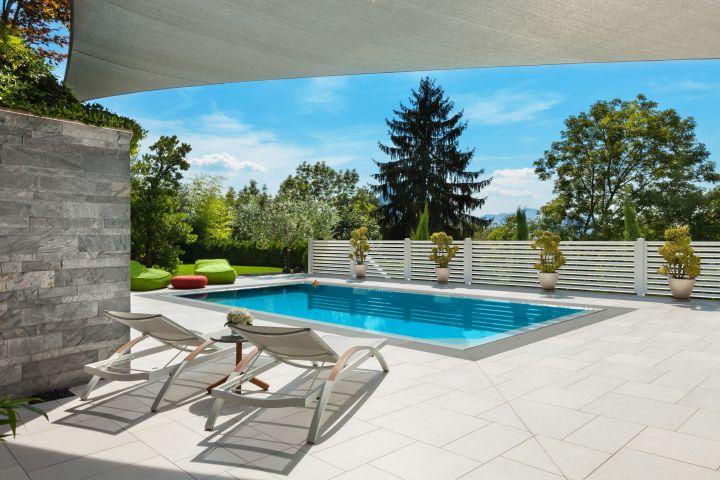 Terrasse mit Pool, im Vordergrund zwei Liegen, im Hintergrund ein Sichtschutz aus Aluminium
