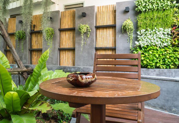 Gemütliche Terrasse mit Bambusstangen als Sichtschutz, im Vordergrund ein Holztisch mit passendem Sessel