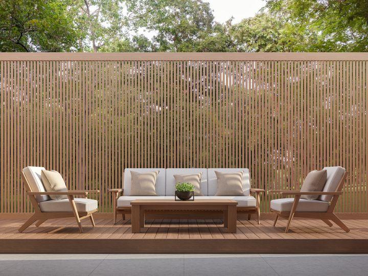 Sichtschutz aus Holz, davor eine Lounge mit weißen Pölstern